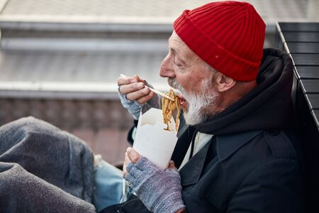 Senior beggar man with grey beard eating food. Poor man wearing old dirty clothes is hungry. Side view