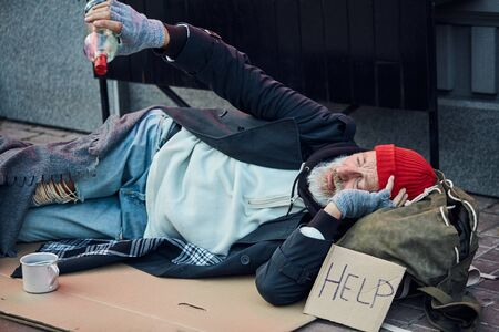 Pitiable dirty bum with sign of help, lie on floor, holding empty bottle of alcohol. Beggar in old clothes in cold weather Stock Photo