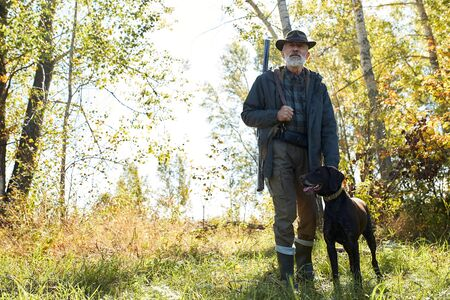 Senior hunter man with his dog in search of trophy, in forest