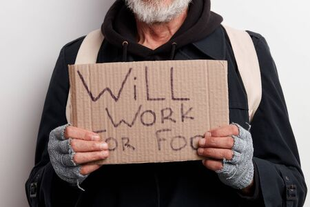 Unrecognizable homeless man holding sign, request for job, seeking help posing at studio over white background