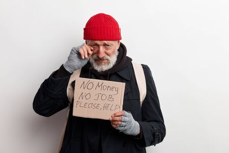 Homeless man holding sign, request for help, seeking help posing at studio over white background