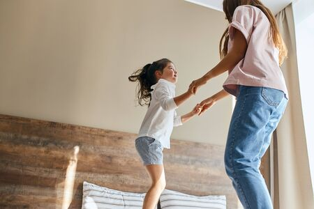 Young mother and little daughter having fun at home, playing together, jumping on bed, spending holidays together, family time concept