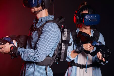 girl and boy in virtual glasses shoots and with virtual weapons isolated on neon light background 版權商用圖片