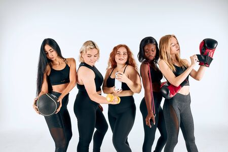 Slim attractive young girls stand together isolated over white background, with balls, dumbbells, healthy and sportive