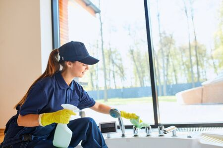 Young caucasian woman janitor cares about new house. Spring general clean up of cleaning service. Commercial cleaning company concept, Panoramic window background