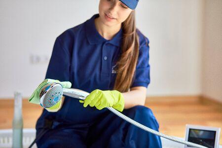 Jeune femme en uniforme de bain de lavage, poignée de douche. Porter des gants de protection jaunes. Concept de service de nettoyage Banque d'images
