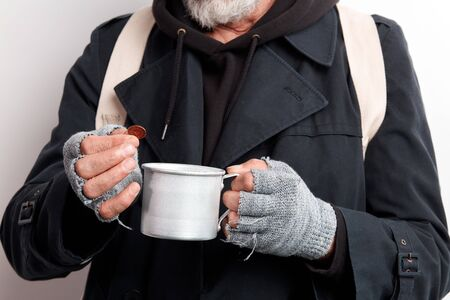 Unrecognizable homeless mature bearded man in black coat and white backpack holding cup for raising money, in one hand a coin. Isolated over white background