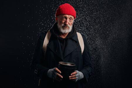 Bearded mature man seeking for help. Sad homeless man under heavy rain wait help Banco de Imagens