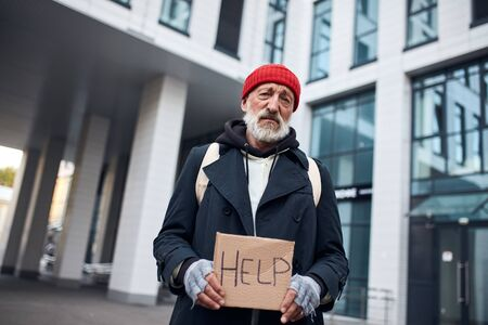 Poor man holding help sign made by cardboard, stand in the center of city, big beautiful business building behind him.