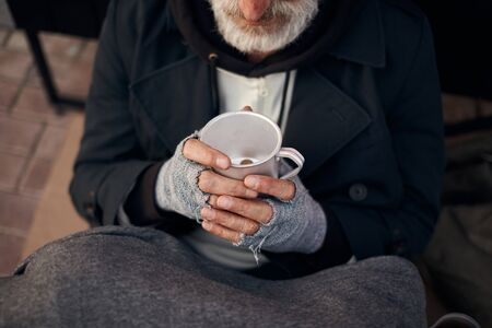 Homeless mans hands holding half empty mug with some coins at bottom. Hands in grey gloves. Poverty, hunger, helpless