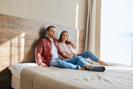 Portrait of charming lady casually dressed sitting happily with young unshaven man on big bed, on background of beautiful curtains and light window, man watching TV hugging on shoulders, family