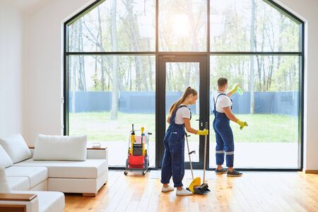 Young cleaners in blue uniform mopping wooden floor, cleaning big panoramic window, preparing country house for selling. Cleaning service concept Imagens