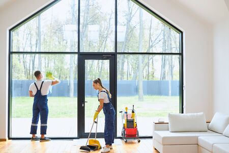Young cleaners in blue uniform mopping wooden floor, cleaning big panoramic window, preparing country house for selling. Successful cleaning service concept