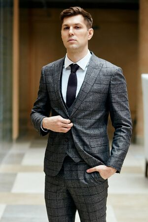 Confident gentleman in grey suit look at camera. People, fashion concept