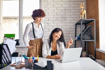 Smiling asian and caucasian women working together in office using laptop, successful team, multiethnic partnership Stock Photo