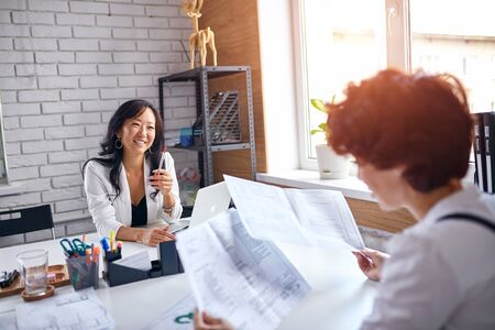 Business for people, cooperation between two sides, asian and caucasian deal. Two business ladies with papers