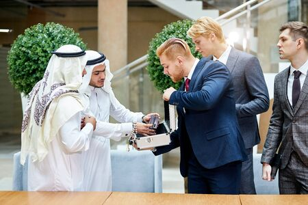 Sheikhs in white suit look at new modern technology in case Stock fotó