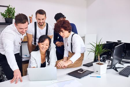 young and enthusiastic people in office, stand near asian woman sitting with laptop. Discuss new project looking at screen of laptop, smiling Stock fotó