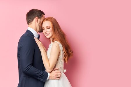 Beautiful woman with red hair hugging her fiance in elegant suit kissing her. Happy young family, love concept