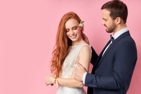 Bearded fiance in love with redhaired woman, long hair. Isolated pink background