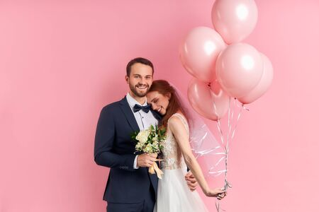 Charming lady with red hair and bearded man prepare to get married with each other, posing isolated over pink background with air balloons. 版權商用圖片
