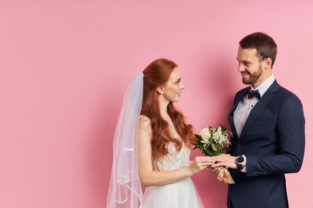Lovely caucasian coule of young woman and man in wedding wear posing at camera isolated over pink background, look at each other