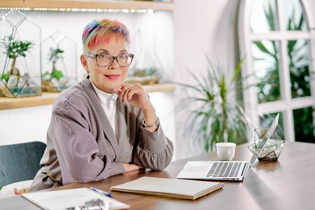 Portrait of open-minded business lady with glasses smile while sitting on table with notebooks and laptop, look at camera. Business people concept