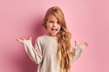 Portrait of charming joyful girl dressed in white blouse with opened mouth, with opened hands, shock or surprise. Posing at camera