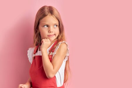 Portrait of coquettish dreamy caucasian kid girl wearing red overalls with long hair looking side isolated over pink background