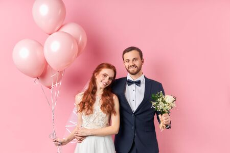 couple in love get married, isolated over pink background happy together, hugging and smiling. Woman holding pink air balloons, man hold wedding bouquet in hands. Look at camera. Wedding, love concept