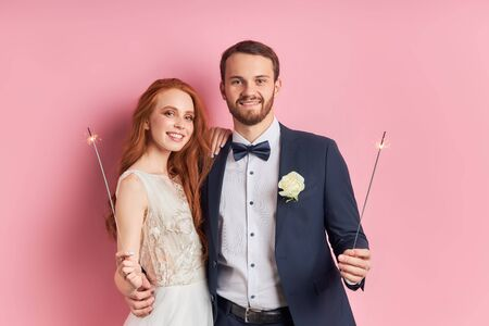 Event,celebration, wedding and love concept. Portrait of young caucasian couple wearing dress and tuxedo holding sparklers isolated over pink background Stock Photo