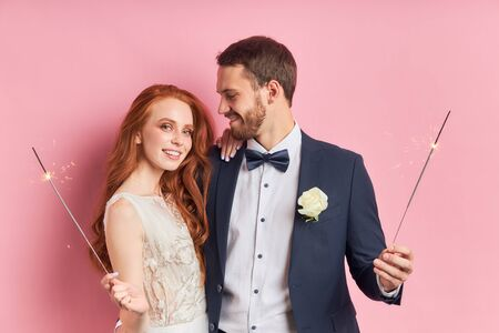 Caucasian couple wearing tuxedo, white wedding dress. Happy two people hold sparklers in hands. Love concept Archivio Fotografico