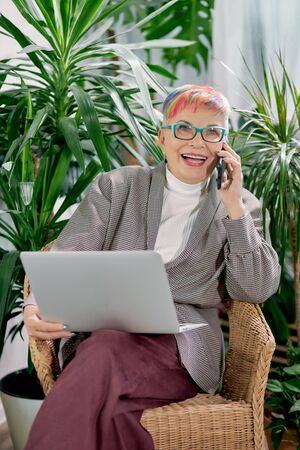 Modern caucasian senior female laught heartily while talking on mobile phone in break. Using laptop, smartphone in work. Businesswoman sitting in business center with plants around