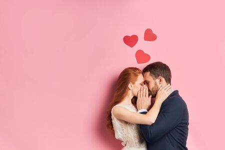 Portrait of young couple hiding ther kiss, love concept Stock Photo - 133236411