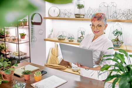 Senior business lady having flower shop stand using laptop, wearing eyeglasses, white suit bathrobe in light room with plants around Stockfoto