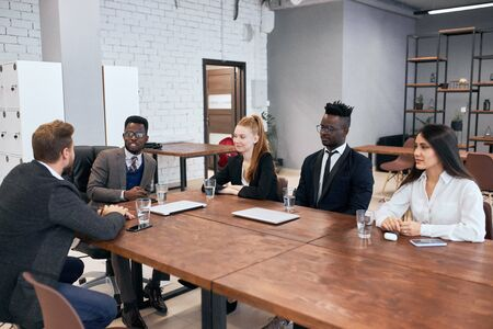 Multi-ethnic young business partners sitting on table having converstion. Young people wearing formal suits. Caucasian and african business partners