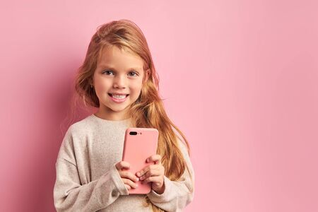 Addicted to phone adorable caucasian girl look at camera fter sending sms to friend isolated over pink background. Mobile phone digital device and children concept