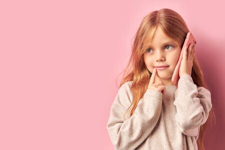 Addicted to phone adorable caucasian girl talking on phone isolated over pink background. Mobile phone digital device and children concept