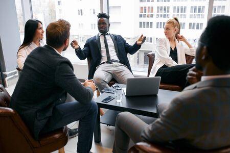 Socios comerciales confiados reunidos en la oficina para discutir interesantes ideas comerciales conjuntas, compartir ideas comerciales