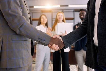 African and caucasian business partners shaking hands each other. Successful deal of business people