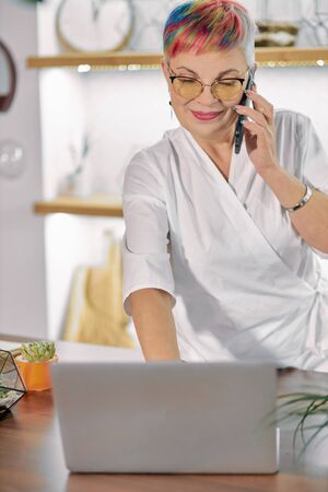 Senior florist woman holding seraching information on laptop and talking on mobile phone. Laptop on table, light room full of plants