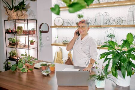 Modern short-haired senior woman engaged in floristy. Caucasian woman in white bathrobe stand talking on phone and using laptop, light room background