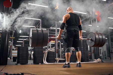 Young hairless bodybuilder keeping heavy weight barbell, standing in white smoke, trying to do deadlift, training in gym, back side view, indoor shot