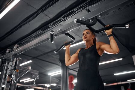Pretty cute female bodybuilder practising with fitness machine, pumping muscles on hands, preparing for workout, look away with confident face, shot from below, professional gym, portrait