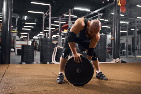 Sporty hairless man training in professional gym, bending in front of barbell, keeping heavy weight plate, looking down, working hard, training for competition