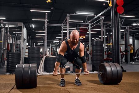 strong hairless man with thick beard, standing on brown floor, holding barbell, ready to do deadlift, looking strong, preparing for workout in gym