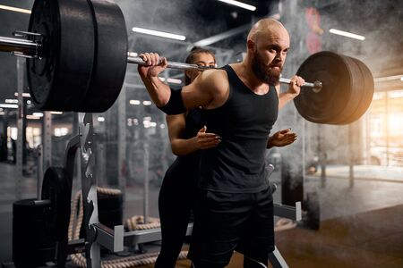 Close view of strong young male powerlifter spending time in gym together with pretty cute female trainer, supporting to lift heavy barbell, training in gym, active people concept Stock Photo