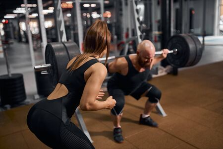 Close up of sporty fit woman standing with back towards camera, supporting brutal powerlifter to stand with heavy barbell on shoulders, practicing in modern fitness studio