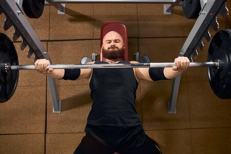 Strong powerful man dressed in black shirt and shorts, having stylish arm bands, lifting heavy barbell, attempting bench press, looking tired, expressing strength, top view Stock Photo