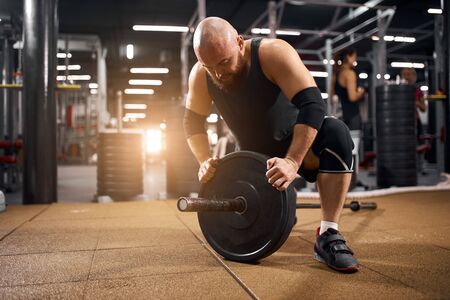 Strong beard weightlifter spending time in gym, working hard, preparing for training, holding weight plate, looking down, expressing powerful feelings, side shot